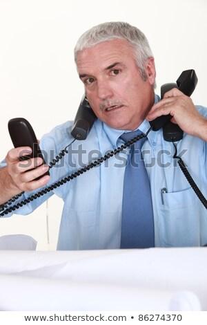 overwhelmed man answering ringing telephones stock photo © photography33