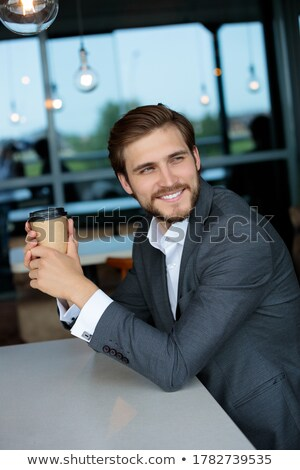 Charming ethnic businessman holding a drinking cup  stock photo © wavebreak_media