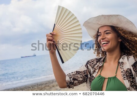 woman holding fan on beach Stock photo © ssuaphoto