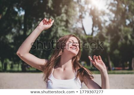 Young beautiful woman raising her hand to dance on the beach Stock photo © wavebreak_media