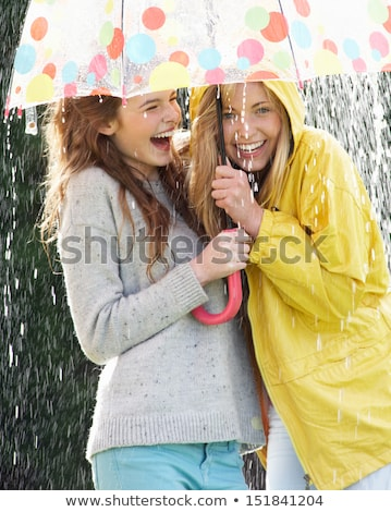 Two Teenage Girl Sheltering From Rain Beneath Umbrella Stock photo © monkey_business
