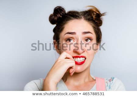 Young woman biting nail and smiling Stock photo © bmonteny