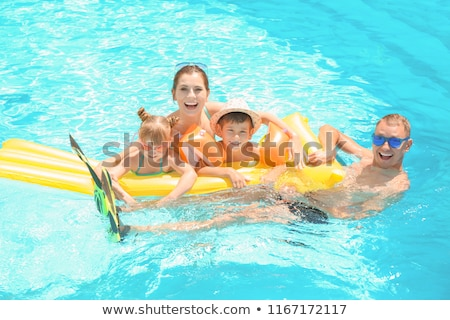 girls resting on air mattress in swimming pool stock photo © deandrobot