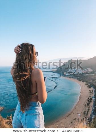 jóvenes · mujer · mar · vista · pie · atrás - foto stock © kzenon