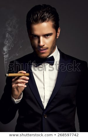 dramatic elegant young man in suit is smoking stock photo © feedough