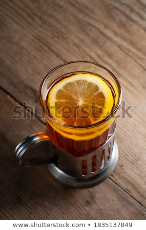 Cup of black tea in a teapot with a lemon and jam on a dark wood Stock photo © Yatsenko