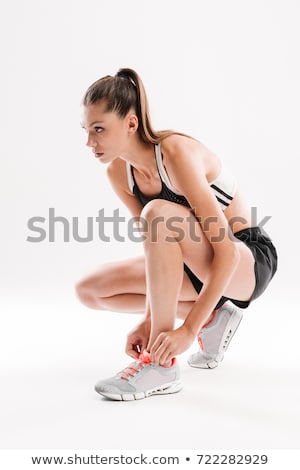 portrait of a young exercise woman tying her shoelaces stock photo © chesterf