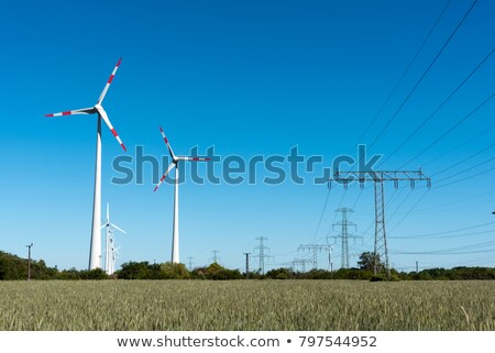 windwheels and power transmission lines in germany stock photo © elxeneize