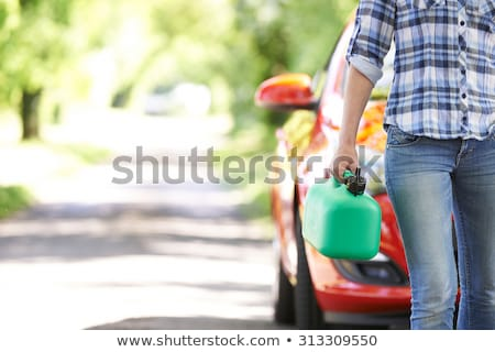 Stock photo: Woman carrying petrol can on the road