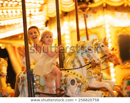mother and kids on a carousel stock photo © is2