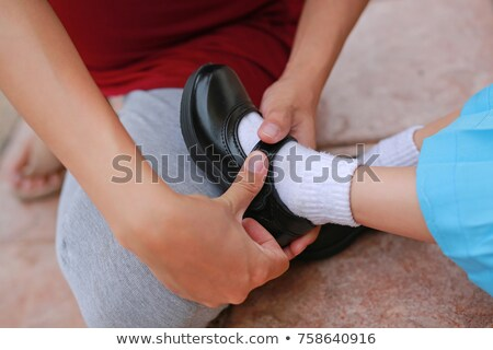 mother helping daughter put on shoe Stock photo © bluering