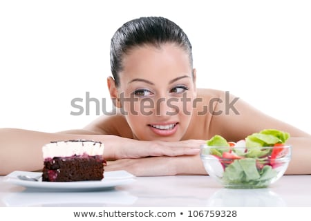 doubting woman with fruits looking at cake Stock photo © dolgachov