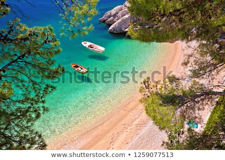 Hiden beach in Brela with boats on emerald sea aerial view Stock photo © xbrchx