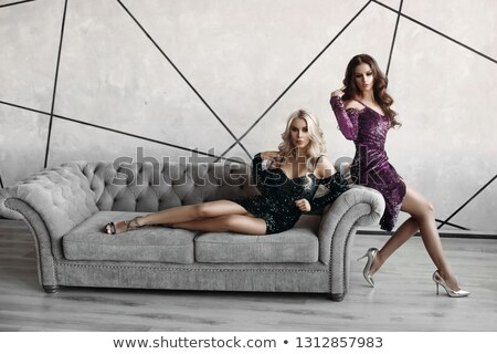 Gorgeous models posing on grey sofa.Two charming and seductive models posing in studio. Stock photo © studiolucky
