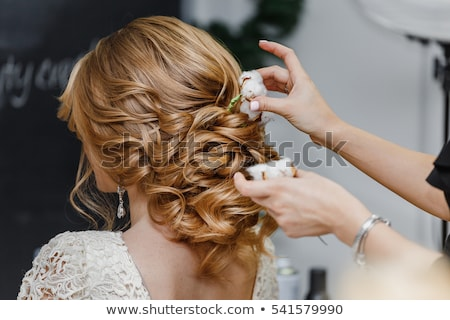 Hair stylist or florist makes the bride a wedding hairstyle with fresh cotton flowers Stock photo © ruslanshramko