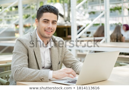 Young confident businessman looking at you while surfing in the net Stock photo © pressmaster