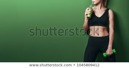 Green smoothies and dumbbells in the gym Stock photo © galitskaya