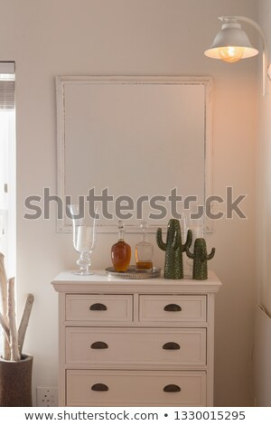 Front view of a modern mirror fixed above a cabinet supporting a vases, bottles of alcohol and false Stock photo © wavebreak_media