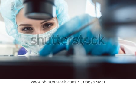 woman doctor working on manipulator fertilizing human eggs stock photo © kzenon
