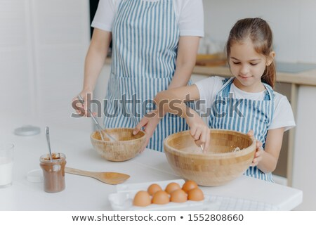 Mother gives culinary lesson to little child, stand next to each other, mix ingredient in big wooden Stock photo © vkstudio
