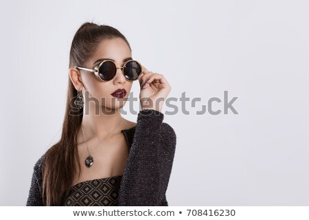The woman on the background of gray walls with long black hair and glasses for vision Stock photo © ElenaBatkova
