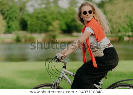 Active Caucasian curly woman looks aside, rides sport bicycle, covers distance and travels in open a Stock photo © vkstudio
