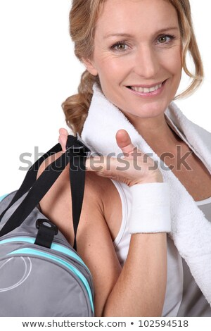 Woman post-workout with a gym bag and towel round her neck Stock photo © photography33
