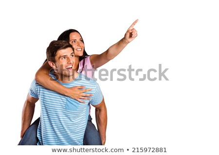 Happy young couple isolated on white piggybacking and finger pointing Stock photo © zurijeta