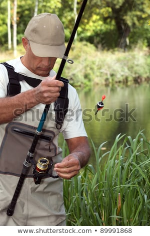 man watching his fishing rod in front of a river Stock photo © photography33