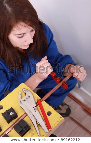 female plumber cutting copper pipe stock photo © photography33