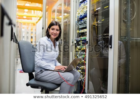 Smiling woman working with servers on laptop in data center Stock photo © wavebreak_media
