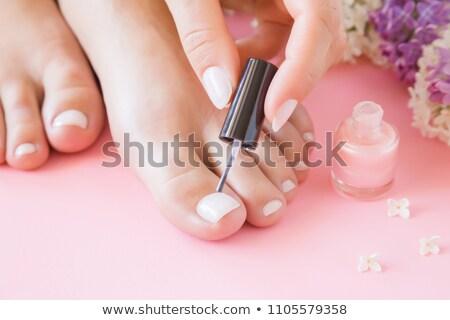 Woman applying nail varnish to finger nails stock photo © wavebreak_media
