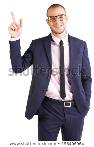A confident young businessman pointing upwards while isolated on stock photo © HASLOO