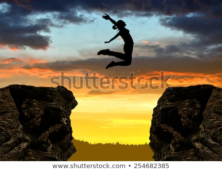 Silhouette of a girl jumping over a rock cliff. Stock photo © DonLand