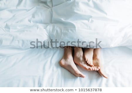 Feet of a couple under the blanket Stock photo © AndreyPopov