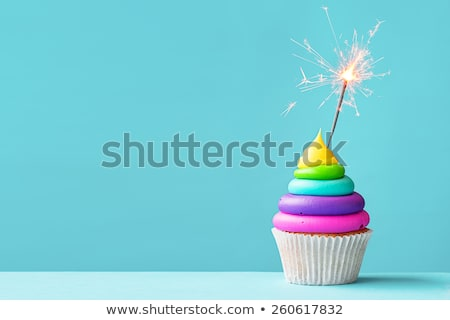 Foto stock: Rainbow Cake And Cupcakes Decorated With Birthday Candles