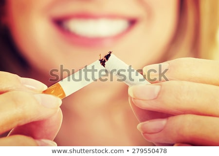Beautiful female smoking a cigarette with smoke in front of face. Stock photo © uleiber