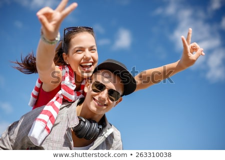 smiling teenager couple with sign stock photo © stokkete