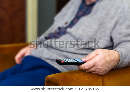 old man on the sofa with television remote control stock photo © ambro