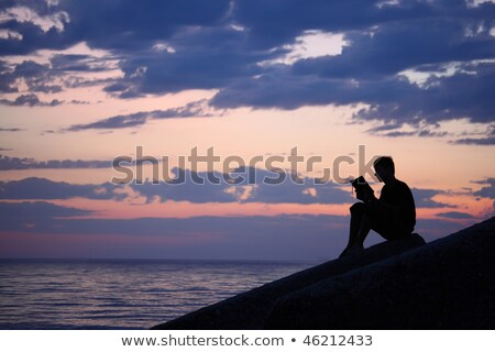silhouette guy sitting on breakwater in evening near sea reads stock photo © paha_l