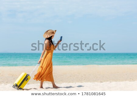 Summer vacation accessories on tropical sandy ocean beach, holidays abroad - summertime lifestyle objects in flat lay top view arrangement in warm sand.