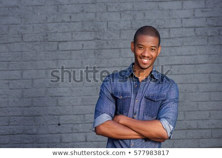 handsome african american young man standing with arms crossed stock photo © deandrobot