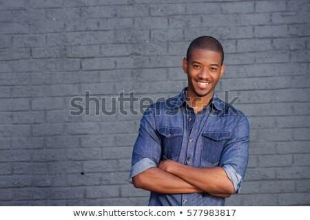Jóképű afroamerikai fiatalember áll keresztbe tett kar szemüveg Stock fotó © deandrobot
