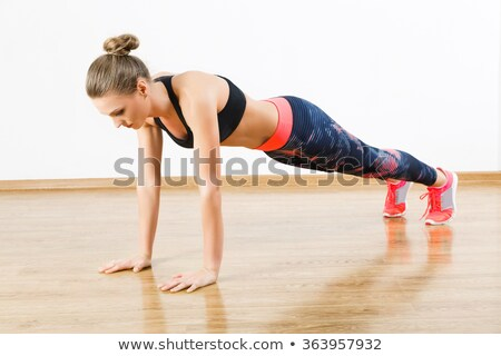 woman doing pushups on white floor stock photo © nobilior