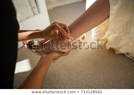 Beautician putting on sandals to bride at home Stock photo © wavebreak_media