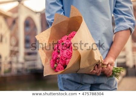 Fiatal divatos férfi tart köteg virágok Stock fotó © konradbak