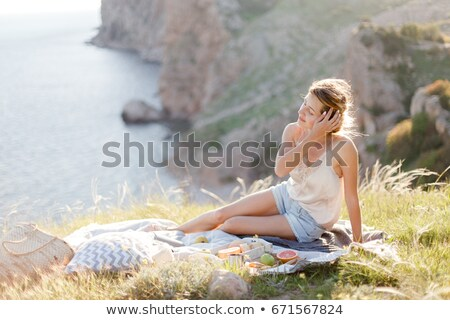 Woman in summer Picnic on the beach at sunset in the white plaid stock photo © Yatsenko