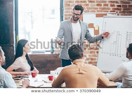 Fiatalember szemüveg asztal iroda kék nadrág Stock fotó © Traimak