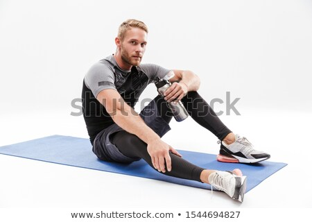 Portrait of a fit sportsman sitting on a fitness mat Stock photo © deandrobot