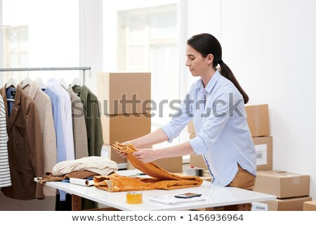 Young casual woman folding yellow velvet pants on desk Stock photo © pressmaster